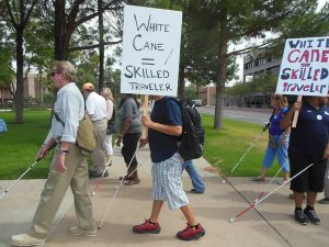 "Students marching on White Cane day holding their canes and carrying signs ""White Canes = Skilled Traveller"""